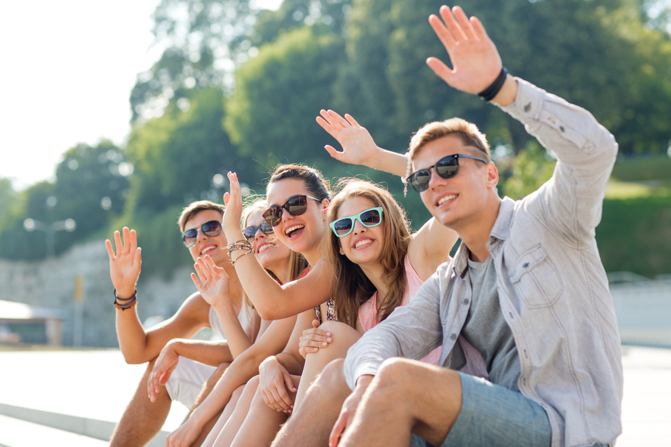 friendship, leisure, summer, gesture and people concept - group of smiling friends sitting on city square